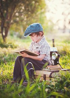 A boy with a mack on his suitcase with books, a camera, and self-desire to read.