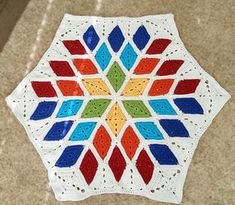 This fun baby afghan was inspired by a quilt I saw on Pinterest. I loved the rainbow colors, and I love the quilted Prairie Star done in crochet.