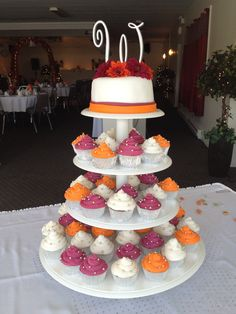 Orange, white, and burgundy wedding cake with cupcakes Decorated by Tammy Good-Redmond