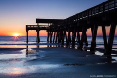 """Sunrise at Tybee Island Pier Tybee Island Georgia """"The Tybee Pavilion located at the end of a pier on Tybrisa Street is used for festivals and other special events throughout the year. The original Tybrisa Pavilion which burned down in 1967 was popular for its crystal ball big bands and dime dances early in the twentieth century.  Tybee Pavilion also became well known during this time as a resort town. A short boat or train ride away from Savannah Savannah Beach promised relief from the…"""