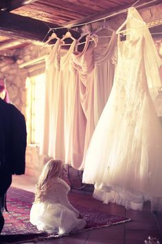 The gorgeous flower girl gazing up at the wedding dress, such a gorgeous photo