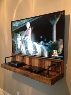 I love this! Wood & pipe shelf for electronics under a wall mounted television.