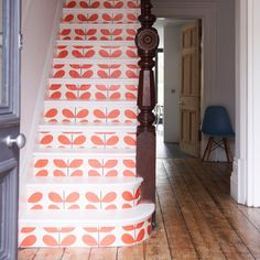 Hallway with white and orange patterned staircase, wood flooring and blue Eames chair