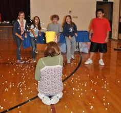 marshmallow game. Divide into 2 teams. One person from each team holds a bucket on their head while the other players try to toss as many marshmallows into their teams bucket as they can in 60 seconds. Mark a line on thw floor that they aren't allowed to cross.