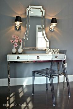 Gorgeous dressing area with Jonathan Adler Channing Three-Drawer Console Table paired with an Uttermost Cattaneo Silver Beaded Mirror flanked by octagonal nickel wall sconces with black shades against a backdrop of dark gray walls with a smoke gray acryli