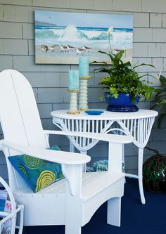 Make your porch feel like a room with wall art, candles and plants. Gray siding, beach art, pillow, white furniture, blue upholstry, Pretty Porches and Terraces