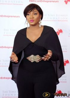 Omotola Jalade-Ekeinde Looks Gorgeous As Rocks A Black Caped Jumpsuit To Tony Elumelu Foundation Programme African Lace Dresses, African Fashion Dresses, Black Dress Accessories, Look Fashion, Fashion Outfits, African Traditional Dresses, African Print Fashion, African Wear, Mode Style