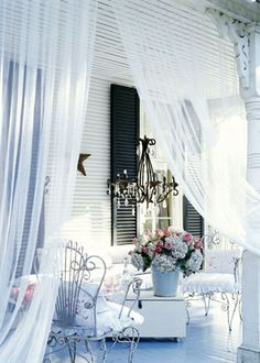 Classic Country ADD ROMANCE ON THE PORCH:   Turn your porch into a romantic destination with sheer curtains and floral fabrics. Sheer curtain panels section off a corner of the porch and painted metal furniture piled with flirty pillows covered in outdoor fabric add comfort. A chandelier with clear prism drops adds drama.
