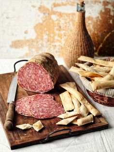 Salami on a cutting board next to crackers and a cheese plate - DIY canapes?