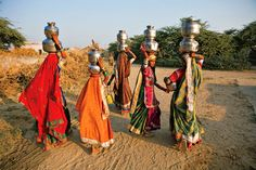 In India's Hodka village, Meghwal women gather to collect and carry water. The hell is their traditional metal pot. The circular huts that are particular to Hodka's mud architecture are also part of the simple and chic Shaam-e-Sarhad