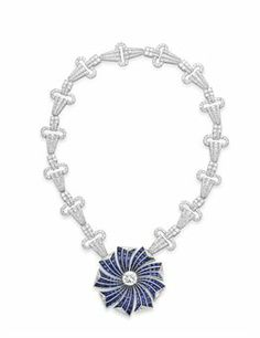 A DIAMOND AND SAPPHIRE NECKLACE  Suspending a calibré-cut sapphire pinwheel, centering upon a circular-cut diamond, weighing approx 4.21 carats, the spokes trimmed with triangular-cut diamonds, to the circular-cut diamond geometric open link neckchain, mounted in platinum, with French assay mark.