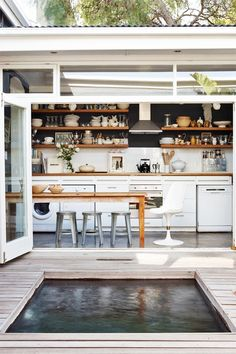Dining space with white walls and cabinets, wood table, wood shelves, and an outdoor pond