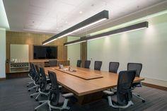 Escritório de empresa de investimentos. Sala de reunião com mesa e estante em marcenaria acabamento Nogueira. Cadeiras Haworth Zody.  Carpete Interface. Projeto de Henrique Grechi por Athié Wohnrath RJ.