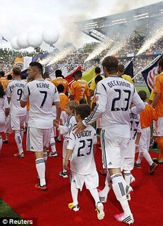 Los Angeles Galaxy's David Beckham walks out to the field with his sons Brooklyn, Romeo and Cruz along with teammates including Robbie Keane (7) before the MLS Cup championship soccer game against Houston Dynamo.12/1/12