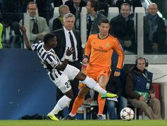 Kwadwo Asamoah of Juventus #22 and Cristiano Ronaldo compete for the ball during the UEFA Champions League Group B match between Juventus and Real Madrid at Juventus Arena on November 5, 2013 in Turin, Italy.