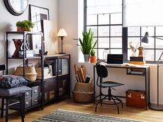 White workspace with wood floors and industrial style black metal and wood shelving and desk.