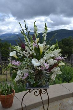 Chic standing arrangement with lilac, calla lily, snapdragons, and greenery. Fleurish Floral Designs
