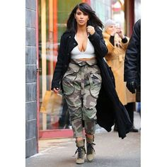 Kim Kardashian's Cleavage-Baring Crop Top and Camo Pants Are You... ❤ liked on Polyvore featuring tops, crop top, star print top, camouflage tops, black top and camo crop top
