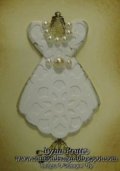 Punch art wedding dress. Punch a strip of cardstock with Lace Ribbon Border Punch. Use the large petal on the Blossom Petals Punch and punch out one in the lace and another of regular white card stock. Do the same with the medium heart. Then glue them on top of each other.