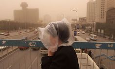 A Beijing resident tries to shield themselves from the Gobi desert dust as it hits Beijing, by wearing a plastic bag over their head.