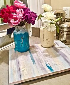 Distressed Mason Jars on a wooden board or wood tray that makes the perfect kitchen decor or centerpiece on your dining table. Mason jars painted in aqua (blue and green) and beige (creamy and off white) chalk paint colors and are great for holding flowers. Mason Jar Centerpiece is ideal for a flower vase and is custom made in the colors of your choice.