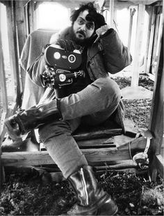 Stanley Kubrick, holding a Bolex film camera, waiting for the rain to stop on shooting A Clockwork Orange.
