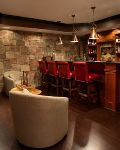 Basement Man Cave Bar with mission-style American Cherry bar, leather nailhead high-back stools, mahogany floors, seating area, stacked stone walls and tray ceilings.