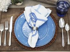 How to Host a Beach-Themed Wedding Shower : Coastal style is known for its casualness, so keep that overall aesthetic in mind when putting together table settings for a beach-inspired wedding shower. To work the blue-gray and natural tones of the design into the tablescape, woven-seagrass chargers were used along with periwinkle dinnerware, navy-blue drinking glasses and antique pewter flatware.  From DIYnetwork.com