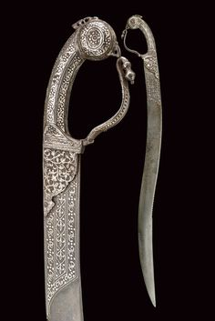Indian sword, 19th century, double curved damascus steel blade with serrated back and floral decorations in silver at the fort; hilt and locking ring made of iron, stylized bird's head pommel, engraved and silver decorated with floral and geometric motifs, length 76.5 cm.
