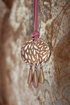A bronze piece handmade with Météor Clay Premium Bronze Rose (a rosy warm shade of bronze) with handmade purple & green shaded glass pendants. To buy online check the link.