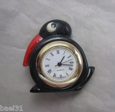 A miniature clock button carved to resemble a vintage bakelite clock design.  This sweet little black bird has a working watch component inserted and can be made into a pin for wearing, used in a doll house, or kept as a collectible button.