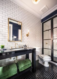 A metal shower enclosure, subway tile and dark grout introduce masculine elements to the gentleman's bathroom at the San Francisco Decorator Showcase 2015. A black marble vanity and black tile floor laid in a basketweave pattern maintain the masculine appeal while softening the design a bit.