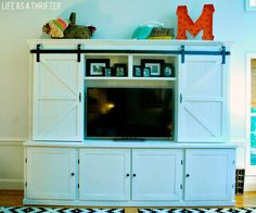Life as a Thrifter: Awesome cabinet with sliding barn doors to hide the TV
