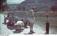 German soldiers speaking with a Sicilian boy as they changed a tire on their Kübelwagen, Sicily, Italy 1943.