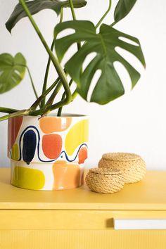 Las plantas grandes como la monstera tienen mucha presencia, por eso necesitan un macetero que esté a su altura. Y te aseguramos que el macetero MARRAKECH no pasa desapercibido :) Esta pieza de cerámica esmaltada en blanco está pintada de colores alegres como el azul, el amarillo y el naranja. Así, la combinación del macetero con la planta hará que tu vestíbulo, salón o dormitorio sea mucho más animado. #planter #ceramic #artesanal #monstera Marrakech, Planter Pots, Enamels, 72 Hours, Orange, Yellow, Blue Nails, White People, Handmade Pottery