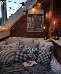 What a cozy reading or cuddle nook this would be!!! the rustic exposed brick wall and the expanse of windows gives it an outdoor feel! -Felicia