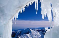 A 'Frozen' world: Amazing icy landscapes - Mount Tasman, and Tasman Sea in distance, seen framed by icicles near the summit of Aoraki/Mount Cook in New Zealand.