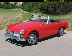 MG Midget MK II. I had one of these when I was 18!! same colour, wire wheels and chromed bumpers. Only put the hood up when it was torrential rain! any other rain, you just drive faster!!