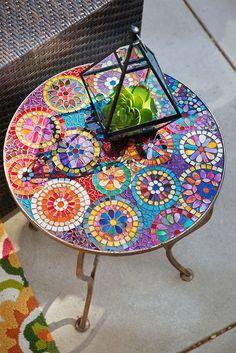 table de jardin ronde avec un plateau décoré soigneusement de mosaïque de verre multicolore