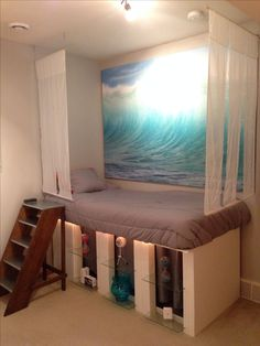 Side 1 of my relaxation room. The room has two main themes, water and New York. On this side a homemade bed with IKEA wave artwork over it. Below are shelves with simple pieces of art and technology, sub themes to the room. The hanging curtains are sheer curtains repurposed for a tropical feel to the bed.