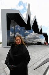 Architect Zaha Hadid stands in front of the museum's glass-facade beneath a three-peaked roofline.