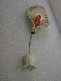 """Vintage Art Deco Celluloid Calla Lily Stick Pin with a White Rose Bakelite End Cap. The brooch is 3.75"""" long and 1.25"""" wide at the widest point of the lily. It has clear rhinestones rimming the lily w"""