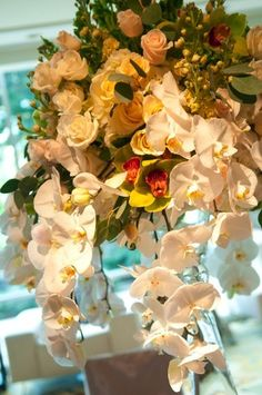 Phalaenopsis orchids cascaded from the towering centerpieces that included three shades of roses (ivory, champagne, and pale yellow) and green cymbidium orchids.