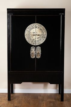 """A vintage Asian-inspired cabinet for a stunning cultural and functional addition to your home decor.  - Black and gold finish  - Elm wood construction  - Iron hardware  - 2 front doors with embellished handles and top sliding pin-key lock  - Removable interior middle shelf   - Approx. 42"""" X 20"""" L x 68"""" H  - Imported"""