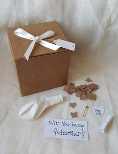 Want to ask will you be my gidmother in a unique way? then how about a balloon in a box? The recipient pops the balloon to reveal the paper confetti and scroll. Our pre filled balloon comes with brown paper confetti which we cut into hearts and butt. Asking Godparents, Balloon Surprise, Godmother Gifts, Fairy Godmother, Godparent Gifts, Paper Confetti, Baby Shower, Will You Be My Bridesmaid, The Balloon