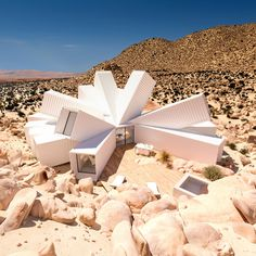 An office with a cluster of shipping containers, initially proposed for a site in London, is now being built in the California desert by James Whitaker.