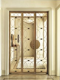 Inspired by the elevator metalwork of old Parisian apartment buildings, the custom bronze and nickel doors crafted by Edelman Metalworks separate the entry foyer from the apartment proper.