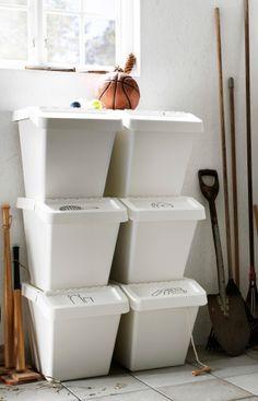 Dans un garage, boîtes de rangement disposées contre un mur et sur l'autre mur, deux étagères métalliques avec du matériel de jardinage et des plantes.