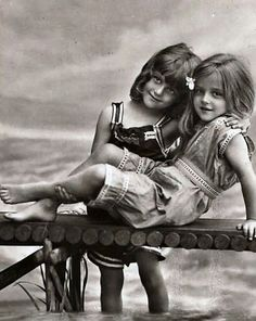 Vintage antique photograph of two little girls on a miniature pier and ocean.