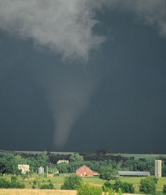 The image shows a tornado in progress northwest of Virgil, Kansas on May 30th, 1982. This is the intermediate stage of the largest tornado I have ever witnessed. It was the third of four tornadoes we would photograph that afternoon and had been on the ground for about 20 minutes. Ten minutes after this photo was taken the funnel faded from sight to our northeast.        These tornadic storms formed on a warm front that was moving slowly across eastern Kansas. It was anchored by a low…